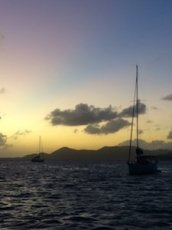 boats sailing the uk virgin islands at sunset